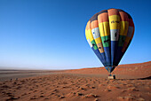 People in a hot-air balloon floating close to the ground, Namibia, Africa