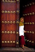 African woman going through a door, Zanzibar, Tansania, Africa