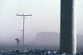 Pedestrian covers his face from sand storm, Iceland