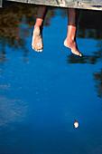 Angler entspannt auf Holzsteg, See bei Boras Vaester Goetland, Schweden