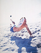 Man jumping in sand playing beach ball, Sylt, North Sea, Germany
