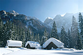Three cabins in winter landscape, Carinthia, Austria