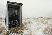 blocked for illustrated books in Germany, Austria, Switzerland: Musterer sitting on an outdoor toilet, Winter, High Country, South Island, New Zealand