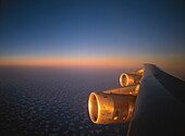 Engine in the warm sunlight from below just before sunset obove small clouds over Arabia