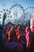 Women wearing saris and ferris wheels in the sunlight, Camel Market, Pushkar, Rajasthan, India