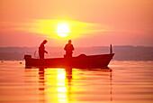 Two men fishing at lake Chiemsee, Upper Bavaria, Germany