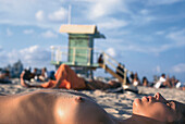 Woman sunbathing topless, Miami, Florida, USA