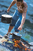 Man cooking in the wilderness, Upper Bavaria, Germany