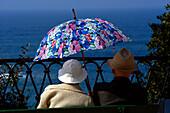 Rentnerpaar auf Bank, mit Sonnenschirm