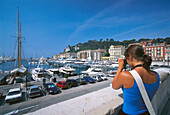 Woman taking a photograph of Nice harbour, Nice, Cote D'Azur, France