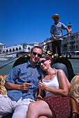Young couple sitting in a gondola, Ponte de Rialto, Canale Grande, Venice, Italy