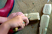 Child carving a wooden figure