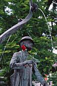 Statue of german humorist Karl Valentin with fountain, Viktualienmarkt market, Munich, Bavaria, Germany
