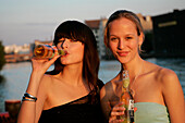Two young women at a beach bar along the Spree, near Oberbaumbruecke, Berlin, Germany