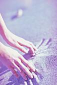 Frauenhaende im Sand, People