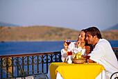 Ein verliebtes Paar trinkt Wein auf der Terrasse in einem Restaurant