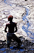 African boy digging hole, people at work