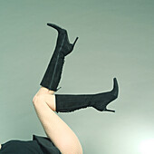 Young woman showing her long legs in the black boots