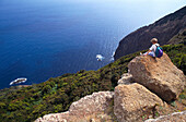 Woman sitting on a rock having a rest, hiking, north coast, Madeira, Portugal