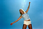 Young woman with outstreched arms against blue sky