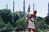 Tea vendor in traditional clothes, Blue Mosque, Istanbul, Turkey