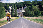 Man riding a mountainbike, Chateau d´ Ussé in the backround, Loire Valley, France