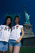 Two smiling girls in front of the Statue of Liberty, Liberty Island, New York USA, America