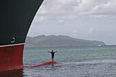 Queen Mary 2, Dangerous remembrance, Queen Mary 2, QM2 Anleger fuer Kreuzfahrtschiffe im Hafen von Fort de France, Martinique. Ein Mann hat sich fuer ein Foto per Schlauchboot auf dem Bugwulst absetzen lassen. Buch S.157