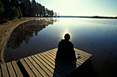 Person sitting on jetty at Suomunjaervi, Patvinsuo National Park, Karelia, Finland