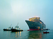Tugboats pulling the cruise ship Queen Mary 2 at dawn, Saint-Nazaire, France