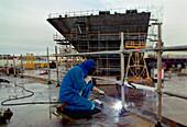 Worker welding steel plates, dry dock, Queen Mary 2, Saint-Nazaire, France