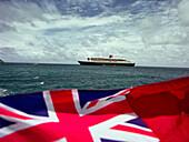 Queen Mary 2 & Union Jack, before coast of St. Maarten