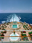 People sunbathing on quarterdeck of the cruise ship Queen Mary 2