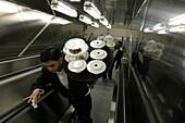 Queen Mary 2, Waiter on a escalator, Queen Mary 2, QM2 Kellner holen ihre bestellten Gerichte in der Hauptkueche ab, Rolltreppe aus der Kueche zum oberen Teil des Britannia Restaurants. Buch S. 149