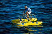Man riding a bike in the water, Sta. Maria de Leuca, Lecce, Puglia, Italy, Europe