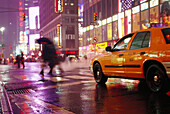 Taxi and people in the rain at night, Times Square, Manhattan, New York, USA, America