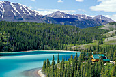 Cabin at Emerald Lake in front of snow covered mountains, Carcross, Yukon Territory, Canada, America