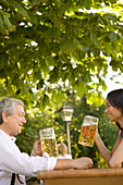 Man and young woman in beer garden, Lake Starnberg, Bavaria, Germany