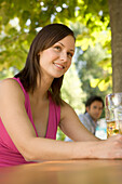 Young women sitting on a bench in beer garden, Munich, Bavaria