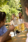 Flirt in beer garden, Two young women and two men flirting in a beer garden, Lake Starnberg, Bavaria, Germany