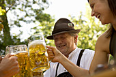 Older Bavarian man and young woman toasting each other, Munich, Bavaria
