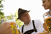 Grandfather and granddaughter looking at each other in beer garden, Munich, Bavaria