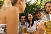 Cheerful people with beer steins in beer garden, Munich, Bavaria