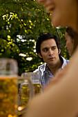 Three cheerful people with beer steins in beer garden, Munich, Bavaria