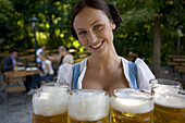 Young waitress with beer steins in beer garden, Munich, Bavaria
