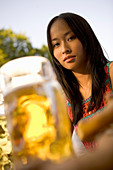 Young woman with beer stein in beer garden, Munich, Bavaria
