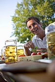 Young man sitting at table with food and beer steins, Munich, Bavaria