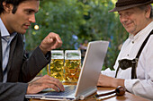 Old Bavarian man and young businessman with laptop in beer garden, Lake Starnberg, Bavaria, Germany