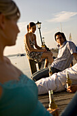 Friends sitting on the jetty with bottles of beer, Lake Starnberg, Bavaria, Germany