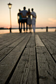 Four young people standing on boardwalk at sunset, Munich, Bavaria